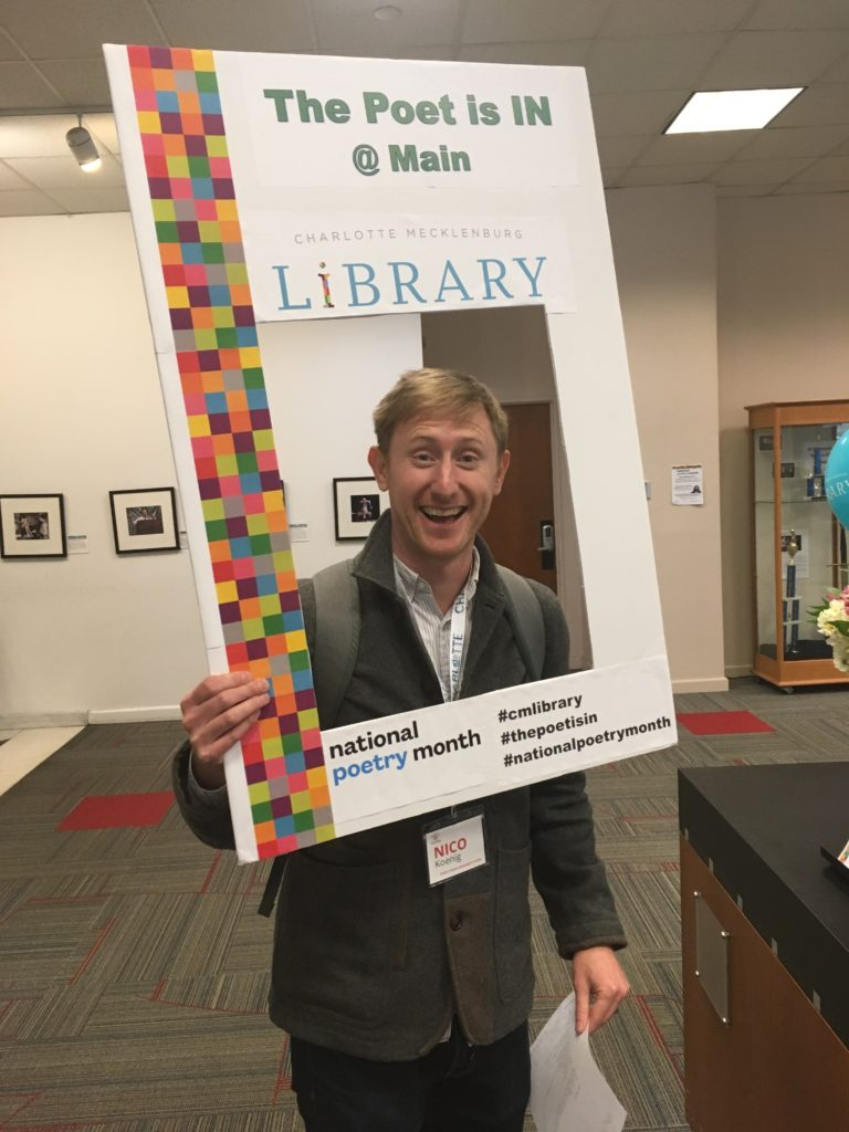 "Nico, a white man with blonde hair, holding up a poster board with a square hole cut out and smiling through the hole. The poster board says ""Charlotte Mecklenburg Library National Poetry Month"" on the edges around his face."